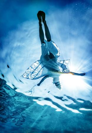 Női sziluett tenger felszínén, fiatal nő élvezi úszni a víz alatt, a kiadások a nyári vakáció a tengerparti üdülőhelyen, aktív életmód fogalmát