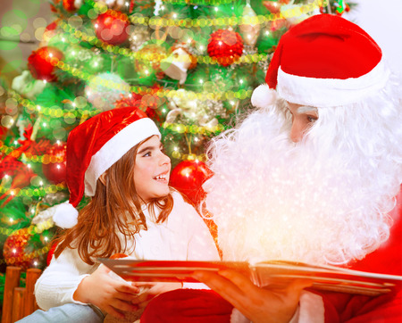 baby near christmas tree: Closeup portrait of adorable baby girl with Santa Claus sitting near beautiful Christmas tree background and reading magical winter fairytale, happy childhood concept Stock Photo