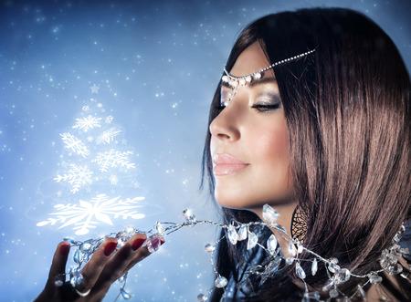 christmas crown: Primer retrato de la hermosa reina de la nieve con la corona en la cabeza sosteniendo en la mano m�gica brillante �rbol de Navidad, la moda de invierno y maquillaje
