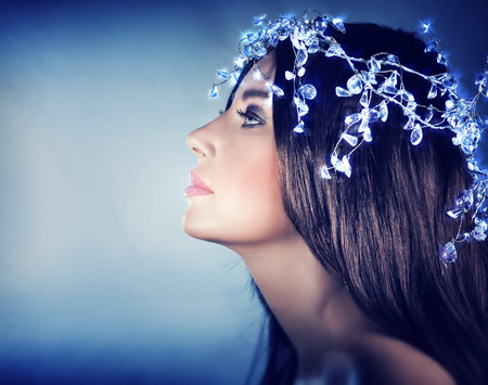 winter fashion: Beautiful snow queen portrait, profile of a gorgeous female wearing stylish shiny head accessories over blue background, fashion for Christmas holidays