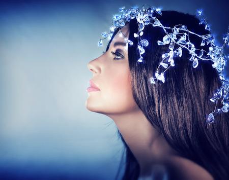 Gyönyörű havas királyné portréja, arcél, gyönyörű nő visel elegáns fényes feje tartozékok fölött kék háttér, divat karácsonyi ünnepek