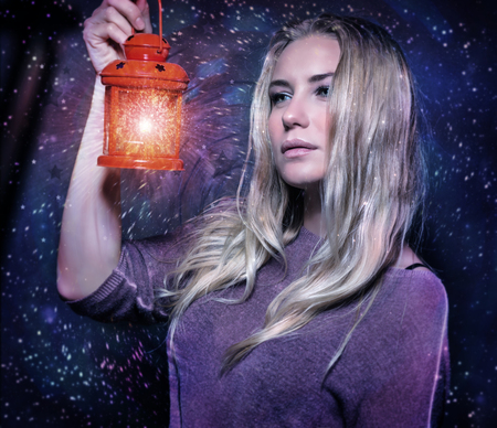 Closeup portrait of beautiful woman with glowing lantern in hands over starry sky, magical Christmas night, fashion concept photo