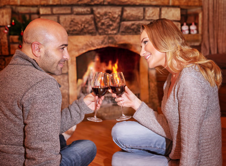 near side: Side view of happy cheerful couple sitting on the floor near fireplace, clinking glasses with tasty red wine, enjoying romantic date