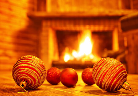 warm house: Cozy Christmas eve at home, beautiful red glass balls on the floor on fireplace background, luxury Christmas tree decoration