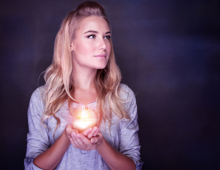 christian candle: Portrait of beautiful blond girl with glowing candle in hands on dark background, praying on Christmas time, traditional Christian holiday