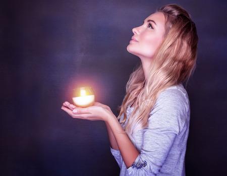 orando: Retrato de la hermosa chica rubia con vela encendida en las manos sobre fondo oscuro, mirando hacia arriba y orar con esperanza, fiesta cristiana tradicional, concepto del tiempo de Navidad
