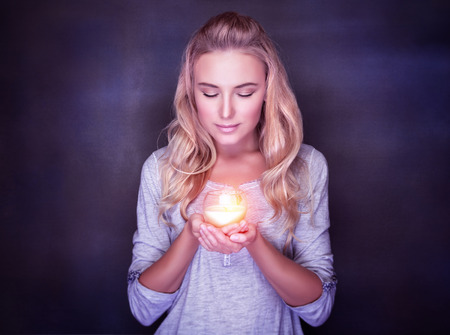 Attractive woman with candle on dark background, calm girl with closed eyes praying, Christmas holidays concept Foto de archivo