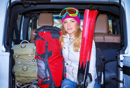 car trunk: Happy girl enjoying winter sports, cheerful portrait of a woman sitting in the car and wearing ski mask, arrived to alpine ski resort, tourist travel on Christmas holidays Stock Photo
