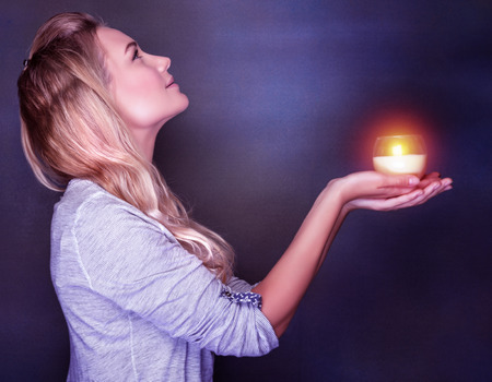 Side view of beautiful woman with candle in hands looking up on dark background, praying about her dreams and wishes, Christmas holiday concept Фото со стока