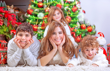 Happy Christmas celebration, cheerful family having fun at home, lying down near beautiful decorated Christmas tree, love and happiness concept photo