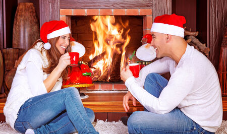 Loving couple by fireplace, young family sitting relaxed in ski resort chalet and drinking coffee, romantic winter vacation, happy people traveling on Christmas holidays Stock Photo