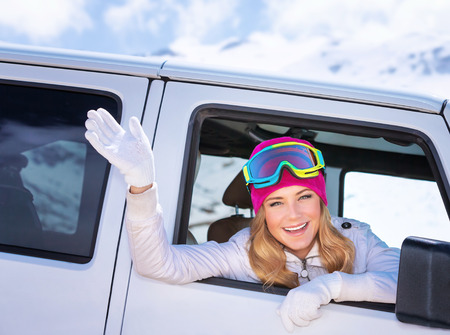 Happy girl enjoying winter sports, cheerful portrait of a woman sitting in the car and wearing ski mask, arrived to alpine ski resort, tourist travel on Christmas holidays Banque d'images