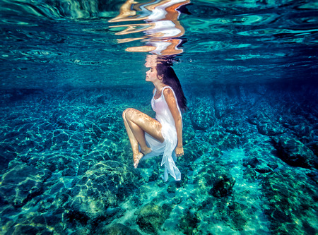 Beautiful dance underwater, gorgeous sportive woman wearing long white dress, dive to clear blue sea, zen balance and meditation concept Archivio Fotografico