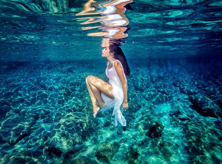 Beautiful dance underwater, gorgeous sportive woman wearing long white dress, dive to clear blue sea, zen balance and meditation concept Standard-Bild