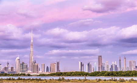 uae: Beautiful Dubai cityscape, pink cloudy sky over luxury arabian town, futuristic modern buildings, expensive resort, travel and vacation concept Editorial