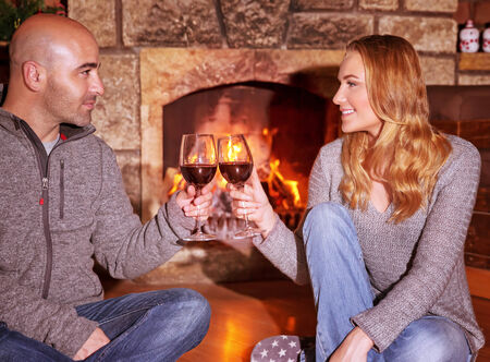fireplace family: Happy young couple sitting near fireplace and drinking wine, enjoying romantic date, celebrating Valentines day in luxury cozy winter resort