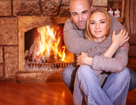 fireplace family: Portrait of gentle couple sitting near fireplace at home, romantic celebration of Christmas holidays, love and togetherness concept Stock Photo