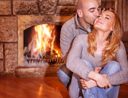 fireplace family: Portrait of gentle couple sitting near fireplace and kissing on luxury ski resort, romantic celebration of Valentine day, love and togetherness concept