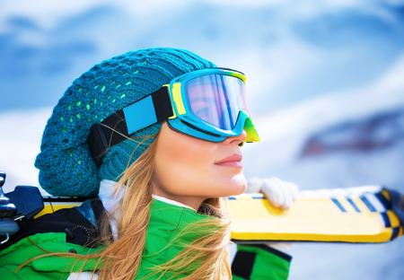 Closeup portrait of beautiful skier girl wearing mask and holding ski, enjoying winter holidays Stock Photo