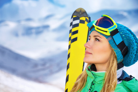 girl glasses: Closeup portrait of beautiful skier girl wearing mask and holding ski, enjoying winter holidays in Europe