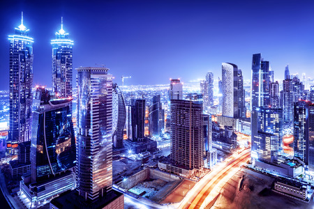 tourism: Dubai downtown night scene, UAE, beautiful modern buildings, bright glowing lights, luxurious travel and tourism