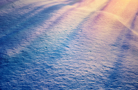 Beautiful snowy background, ground covered with with beautiful fresh snow with yellow sunset light on it, beauty of winter nature photo