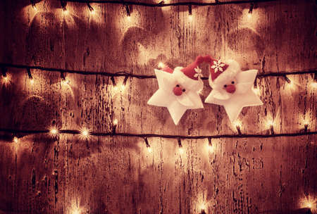 Photo of abstract Christmas glowing background, yellow electrical garland on old wooden door, shiny decorations on dark grunge wall, two Santa Claus stars, New Year festive ornament photo