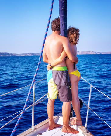 Back side of happy young couple standing on the deck of luxury sail boat, romantic date in sunny summer day, enjoying each other concept photo