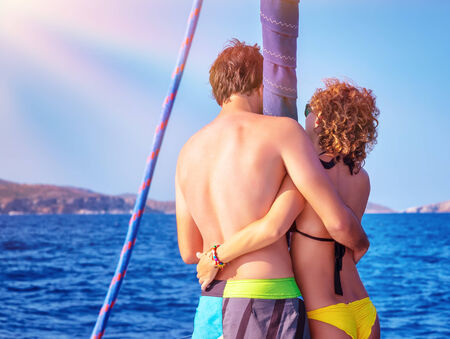 happy young couple: Back side of happy young couple standing on the deck of luxury sail boat, romantic date in sunny summer day, enjoying each other concept