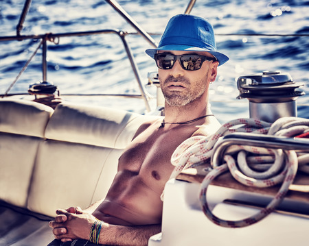 Sexy sailor, man on sailboat enjoying cruise, vintage style photo of a handsome shirtless model sailing on a luxury water transport, fashion lifestyle concept Stockfoto
