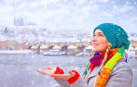 prague: Portrait of cute happy woman enjoy snowfall in beautiful Prague city, catches snowflakes by hands with pleasure, enjoying winter holidays