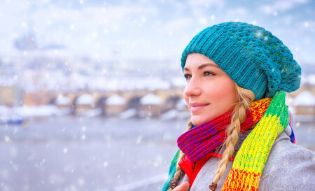 Portrait of cute happy woman enjoy snowfall in beautiful Prague city, wearing stylish colorful hat and scarf, enjoying winter holidays photo