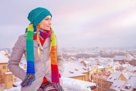 travel destinations: Cute female sitting on the roof of high building and enjoying beautiful Prague cityscape covered with snow, winter vacation concept
