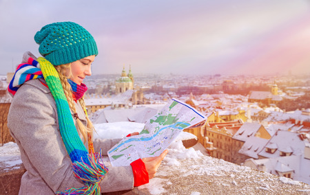 Cute traveler girl searching right direction on the map, standing on the roof of building and enjoying beautiful winter cityscape, travel to Prague Stockfoto