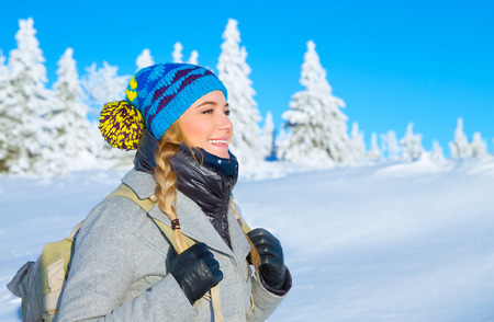 Portrait of happy cute girl traveling along snowy mountains, enjoying wintertime nature, active lifestyle, winter vacation concept photo