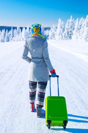 mujer con maleta: El viajar a los Alpes, parte trasera de una mujer joven que recorre a lo largo de camino cubierto de nieve con el equipaje verde elegante, vacaciones de invierno en Europa