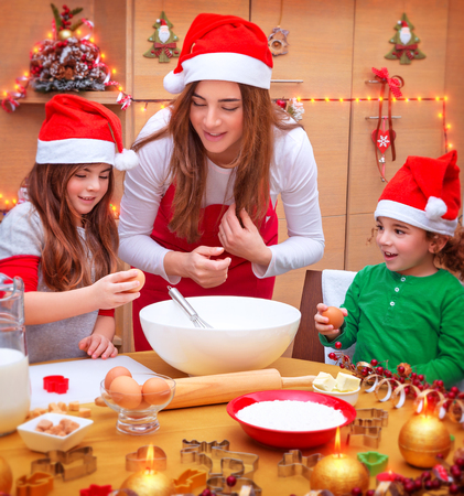 female child: Happy mother with two cute kids wearing red Santa hat cooking festive food on the kitchen, Christmas holidays concept