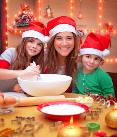 christmas baking: Portrait of cheerful young family preparing to Christmas dinner, mother with two kids cooking at home wearing Santa hat Stock Photo