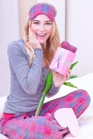 Happy excited woman sitting on the bed wearing cute pajama and enjoying flowers and romantic gift in Valentine day photo
