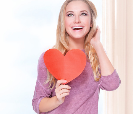 Portrait of beautiful happy girl holding in hands red heart shaped greeting card photo