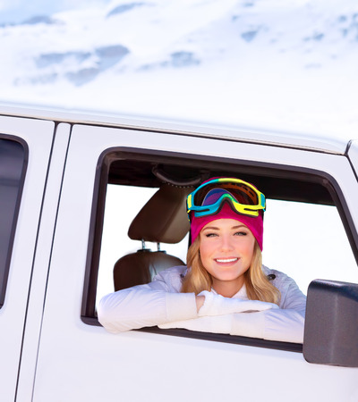 Portrait of cute happy woman in the car going to the ski resort photo