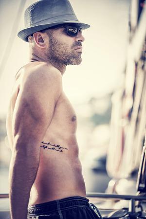 hombres sin camisa: Foto del estilo de la vendimia de marinero sexy sin camisa en velero, hombre curtido con estilo de tatuaje que llevaba sombrero de moda y gafas de sol de relajaci�n en el transporte de agua de lujo