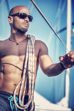 Sexy shirtless sailor portrait, young handsome man standing on the deck of sailboat  with rope on shoulder in bright sun light, active lifestyle, summer vacation concept 版權商用圖片