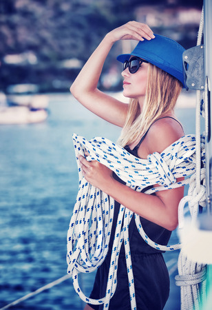 sailor girl: Sexy girl standing on sailboat with rope, vintage style photo of attractive sailor girl, active lifestyle, summer vacation concept Stock Photo