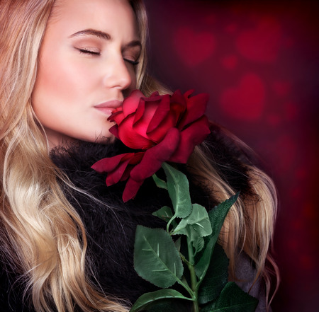 Closeup portrait of beautiful blond woman with closed eyes smelling fresh red rose on background with heart ornament, happy Valentine day concept photo