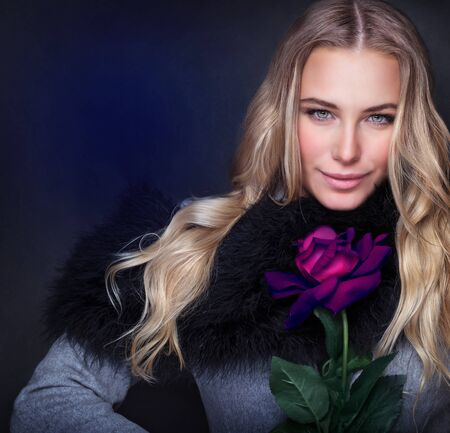 purple rose: Portrait of sexy attractive woman wearing stylish coat holding in hand beautiful purple rose isolated on dark blue background, happy Valentine day, style and fashion concept