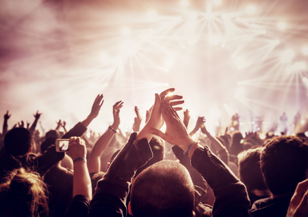 Vintage style photo of a crowd, happy people enjoying rock concert, raised up hands and clapping of pleasure, active night life concept Stock Photo