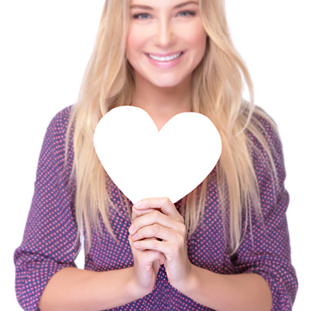 Closeup soft focus portrait of beautiful blond girl holding in hands paper heart isolated on white background, healthy lifestyle or Valentine day celebration photo