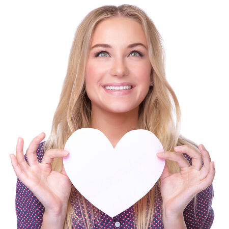 Closeup portrait of beautiful blond girl holding in hands paper heart isolated on white background, healthy lifestyle or Valentine day celebration photo