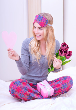 Romantic morning in Valentine day, cute girl receive tulips, gift box and reading greeting card, love and romance concept photo